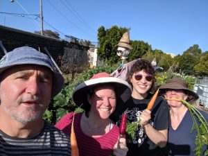 Pentridge Community Garden members holding carrots in front of the bluestone wall